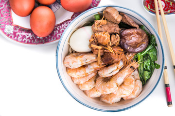 Bowl of Chinese birthday noodle with seafood, meat, red eggs