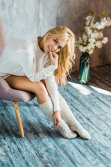 smiling attractive woman in sweater sitting on armchair in bedroom and  looking at camera
