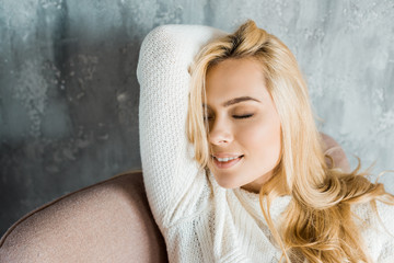 smiling attractive woman in sweater sitting on armchair with closed eyes in bedroom