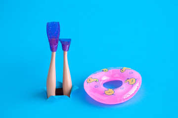 Doll legs with snorkel fins and inflatable pool float on blue sea background minimal creative abstract concept.
