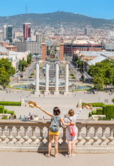 Girls friends with backpacks hug and enjoy the view of Placa de Josep Puig i Cadafalch in Barcelona, Catalonia