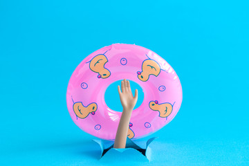 Doll hand from the water with inflatable pool float minimalistic abstract.