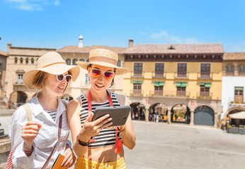 vacation and travel concept - two beautiful girls toursits looking into tablet pc in the old city in Europe
