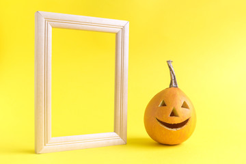 Jack o lantern and wooden picture frame against yellow background.