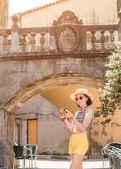 Young woman with digital gadget in the old historical streets of Spain