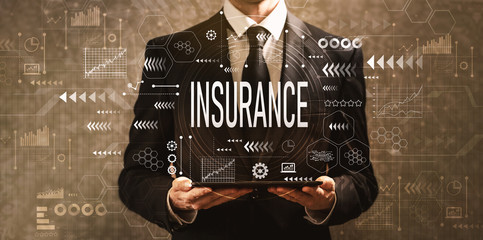 Insurance with businessman holding a tablet computer on a dark vintage background