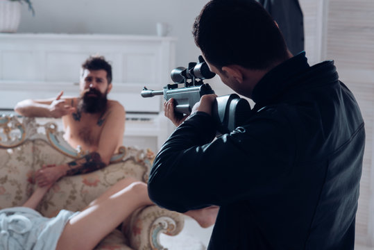 Cheating and jealousy concept. Husband found lovers, killed wife and threatening to bearded lover. Man with beard naked, pray for mercy at gunpoint, interior background. Man at gunpoint of killer