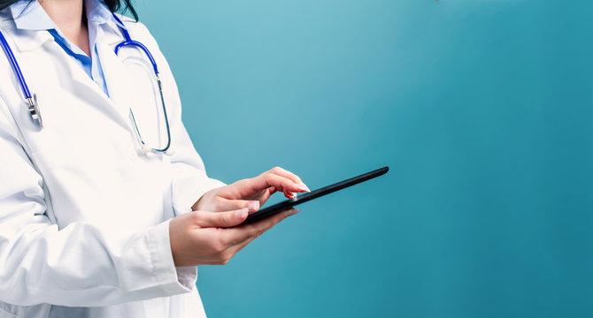 Medical doctor with digital tablet on a blue background