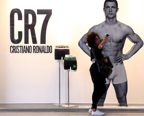 A woman takes a selfie picture with mobile phone in front of Juventus soccer player Cristiano Ronaldo underwear advertising panel in downtown Milan