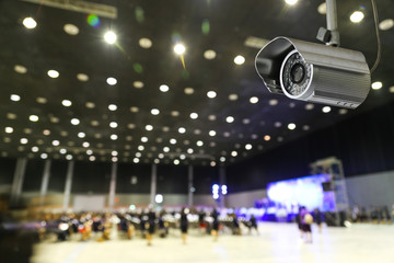 CCTV monitoring, security cameras. Backdrop with views of Exhibition Hall and people background.