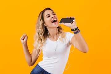 Image of beautiful woman wearing earphones singing while holding cell phone as microphone, isolated over yellow background Fotobehang