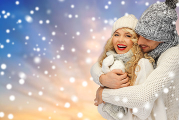 winter, holidays, christmas and people concept - smiling couple in sweaters and hats over snow background