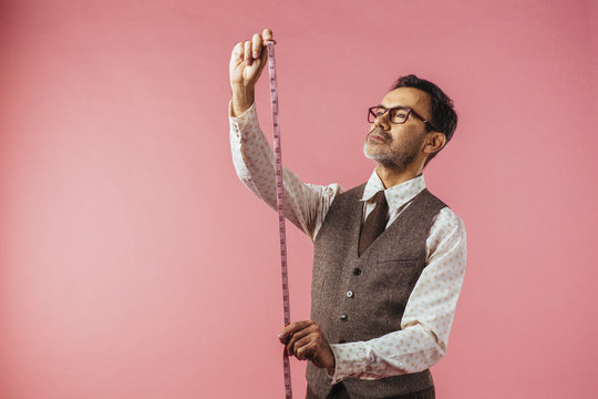 Horizontal portrait of a tailor holding fabric measure, isolated on pink studio background