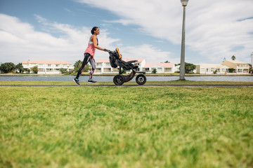 Mother running with a baby stroller in park