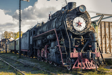 Vintage black steam locomotive train with wagons on station.