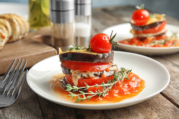 Baked eggplant with tomatoes, cheese and thyme on wooden table