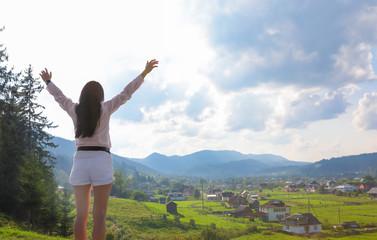 Young woman enjoying beautiful view of village in mountains
