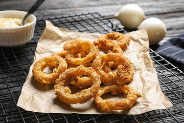 Cooling rack with homemade crunchy fried onion rings and sauce on wooden background