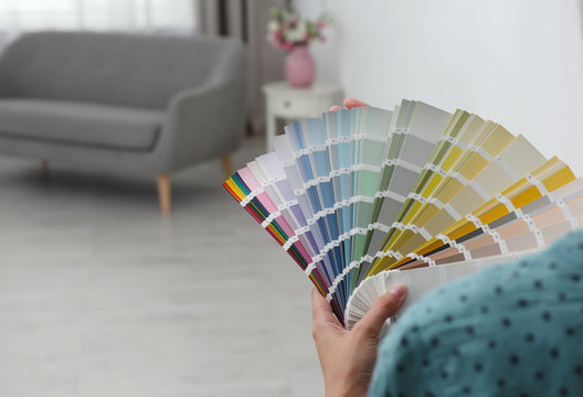 Female interior designer with color palette samples indoors, closeup. Space for text