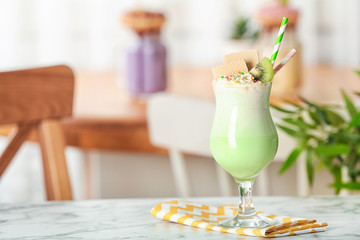 Glass with delicious milk shake on table against blurred background. Space for text