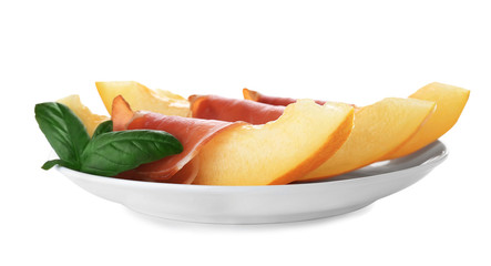 Plate with melon slices and prosciutto on white background