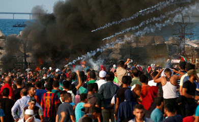 Tear gas canisters are fired by Israeli forces at Palestinians during a protest calling for lifting the Israeli blockade on Gaza, at the maritime border with Israel, in the northern Gaza Strip