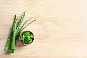 Flat lay composition with aloe vera leaves and space for text on wooden background