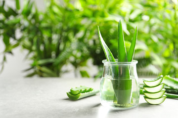 Jar with fresh aloe vera leaves on table against blurred background. Space for text