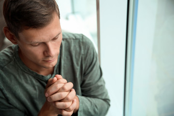 Man with hands clasped together for prayer near window. Space for text
