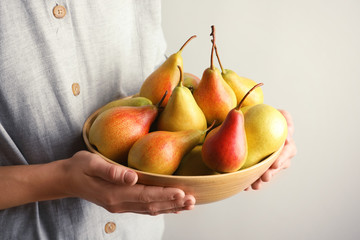 Woman holding bowl with ripe pears on light background, closeup