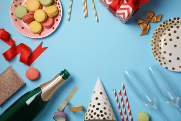 Creative flat lay composition with bottle of champagne and party accessories on color background. Space for text