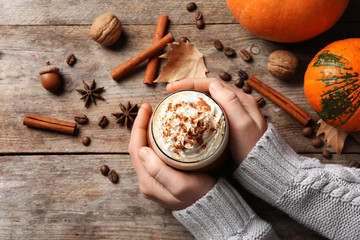 Woman holding glass of tasty pumpkin spice latte on wooden table, flat lay composition