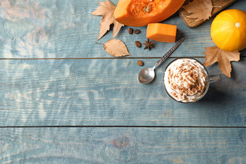 Flat lay composition with glass cup of tasty pumpkin spice latte and space for text on wooden background