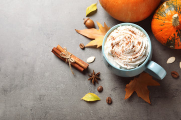Flat lay composition with cup of pumpkin spice latte and space for text on gray table