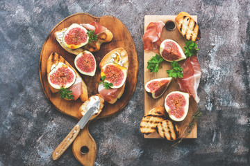 Prosciutto with figs . Fresh figs with ham and cheese on a cutting board, rustic background. Appetizing snack. Top view,toned photo