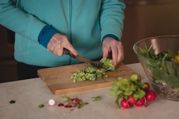 Woman chopping broccoli with knife on chopping board
