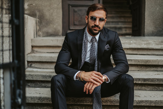 Businessman sitting on the stairs and holding watch