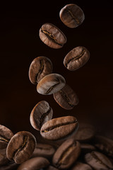 Roasted coffee beans falling on pile. Dark colors