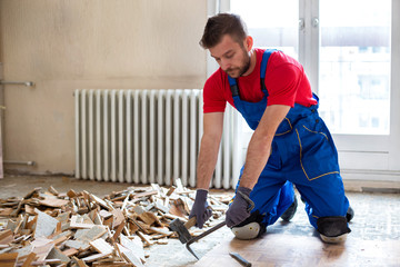 Handyman during work of removing old flooring
