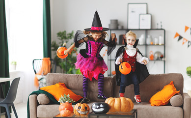 happy children in costumes of witch and vampire are preparing   home for Halloween Wall mural