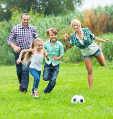 Family of four playing football on field