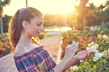 Girl taking smartphone photo to rose flower