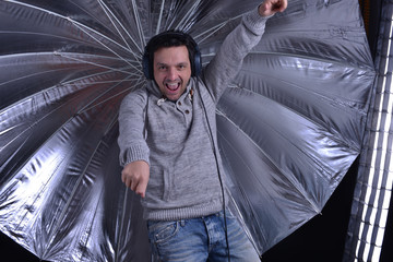 Young man holding a silver umbrella in the studio, smiling, being enthusiastic.