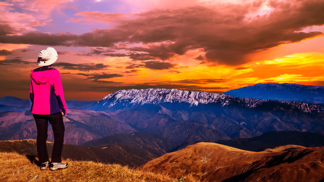 Stunning sunset over the mountains ridge. Woman sitting on a mountain top and looking to the sunset over the mountains in front of her.