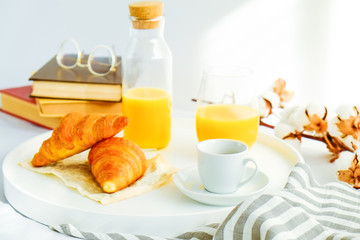 Morning breakfast in bed, white tray with glass of fresh orange juice, cup of coffee and french croissant, vintage eye glasses and books, stripped blankets. Close up, top view, background, copy space.