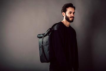 Stylish young guy wearing black blank  and backpack, horizontal studio portrait