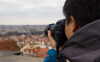 Man looking into DSLR camera and taking photo of Prague landscape in Europe