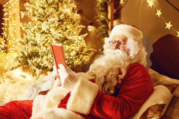 Santa Claus is reading a book in a room with a fireplace in Christmas.