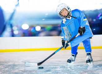 Happy little hockey player passing the puck