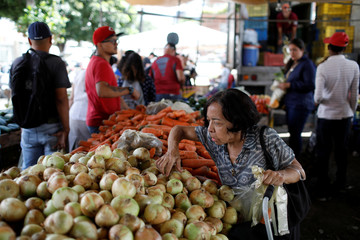 A woman selects onions at a vegetable and fruit stall at a street market in Caracas